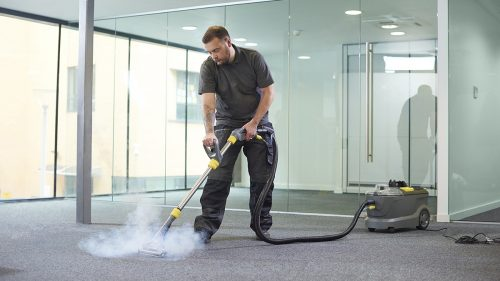 Middle aged man steam cleaning the office carpet